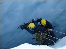photo of rope access specialist assisting cameraman in ice crevasse in Norway